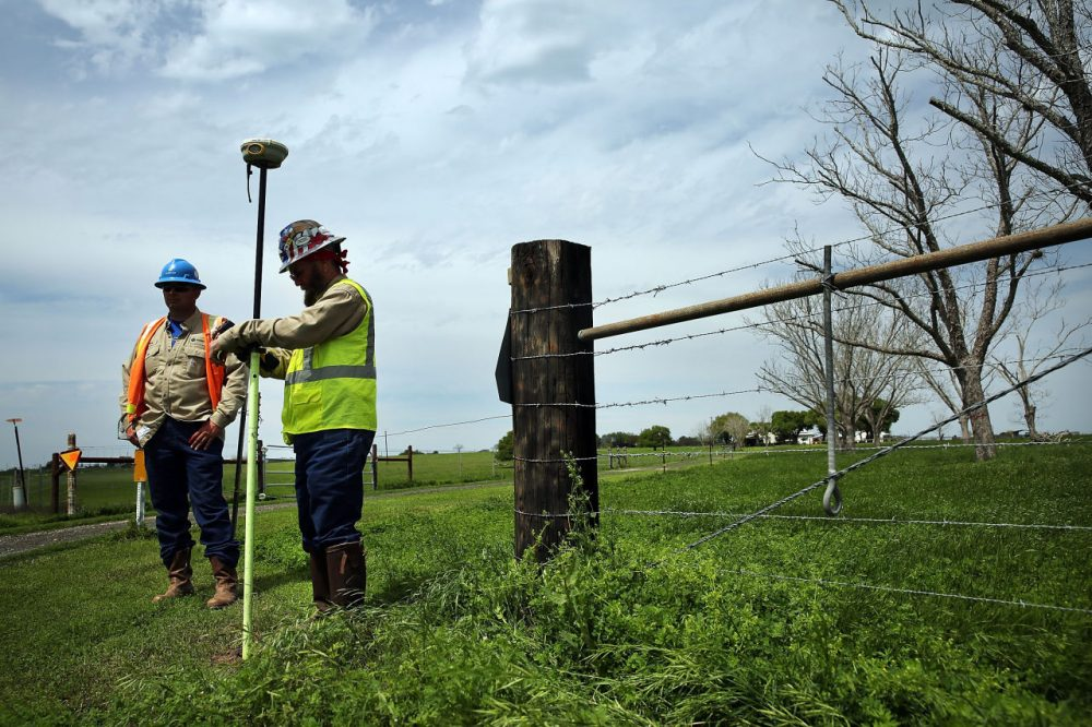 Workers with the oil industry takes GPS coordinates for the laying of new pipe outside of the town of Cuero, Texas. (Spencer Platt/Getty Images)
