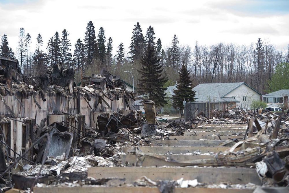 Untouched homes are seen in the background as others destroyed by fire are seen in the foreground in the Abasands neighbourhood during a media tour of the fire-damaged city of Fort McMurray, Alberta, May 9, 2016. (JONATHAN HAYWARD/AFP/Getty Images)