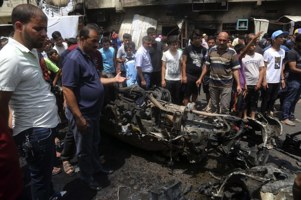 Citizens inspect the scene after a car bomb explosion at a crowded outdoor market in the Iraqi capital's eastern district of Sadr City, Iraq, Wednesday, May 11, 2016. An explosives-laden car bomb ripped through a commercial area in a predominantly Shiite neighborhood of Baghdad on Wednesday, killing and wounding dozens of civilians, a police official said.  (Khalid Mohammed/AP)