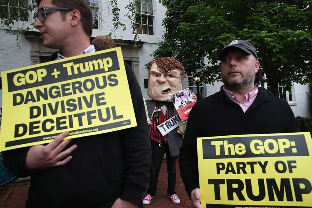 Protesters gather outside of the RNC headquarters where Republican presidential candidate Donald Trump is meeting with House Speaker Paul Ryan (R-WI), May 12, 2016 in Washington, DC. Ryan hopes the meeting to focus on substantive efforts at finding common ground to bridge the Republican party. (Photo by Mark Wilson/Getty Images)