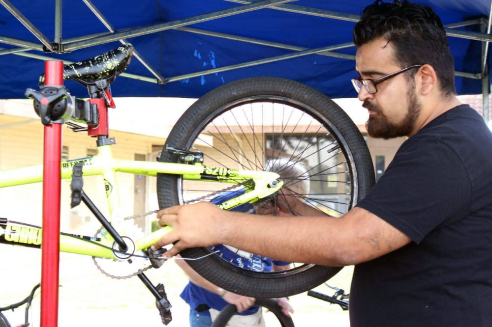 Jaime Rangel volunteers as a bike mechanic at a free event in Fresno on March 18. Rangel, 26, says biking was a lifesaver and helped him get rid of his Type 2 diabetes as a teen. (Farida Jhabvala Romero/KQED)
