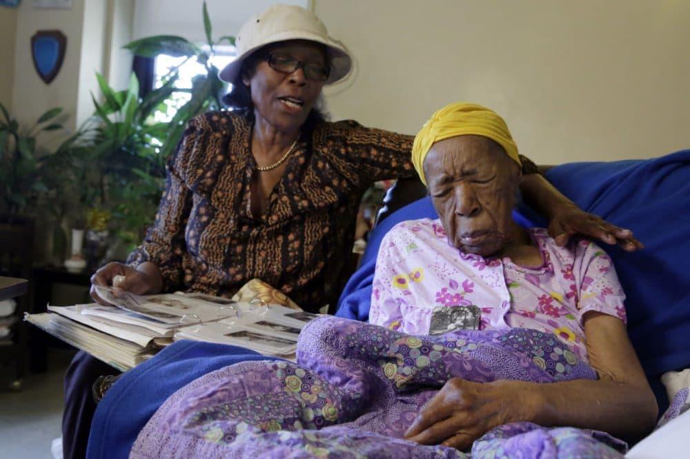 In this Monday, June 22, 2015 photo, Lois Judge, left, looks at a photo album with her aunt Susannah Mushatt Jones, 115, in Jones' room at the Vandalia Avenue Houses, in the Brooklyn borough of New York. Jones and (AP Photo/Richard Drew)