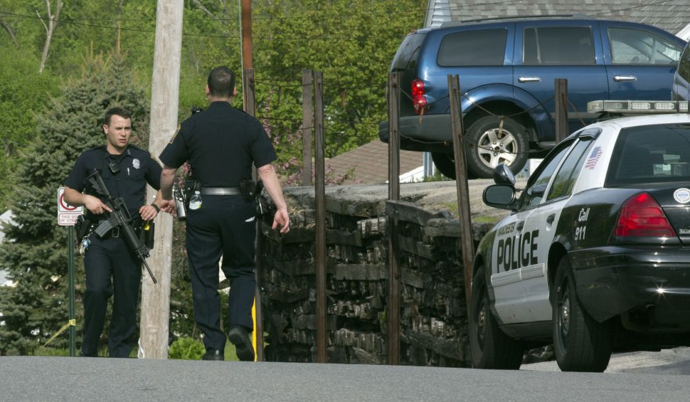 Officers in Manchester, N.H. participate in a search for the suspect in the shootings early Friday. (Jim Cole/AP)