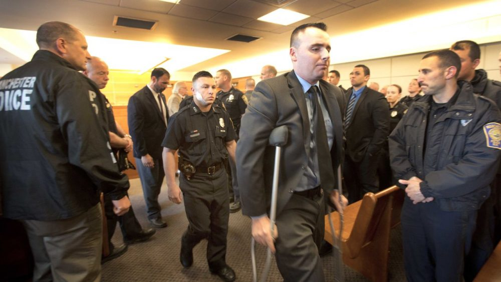 Matthew O'Connor, on crutches, and Ryan Hardy, behind him, leave the courtroom in Manchester, N.H. on Monday after attending a hearing for Ian MacPherson. MacPherson is charged with shooting both officers last week. (Jim Cole/AP, Pool)