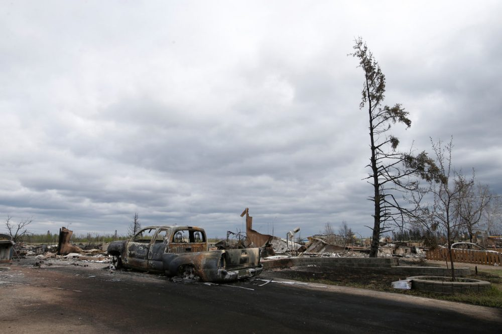 A charred vehicle and homes are pictured in the Beacon Hill neighbourhood of Fort McMurray, Alberta, Canada, May 9, 2016 after wildfires forced the evacuation of the town. Fort McMurray is still 90-percent intact despite a week of damage from the wildfires devastating Canada's oil sands region, Alberta's premier said after touring the deserted city on Monday. Firefighters warned however that the tens of thousands of residents evacuated from the western oil city would not be able to return for at least two weeks. (Chris Wattie/AFP/Getty Images)