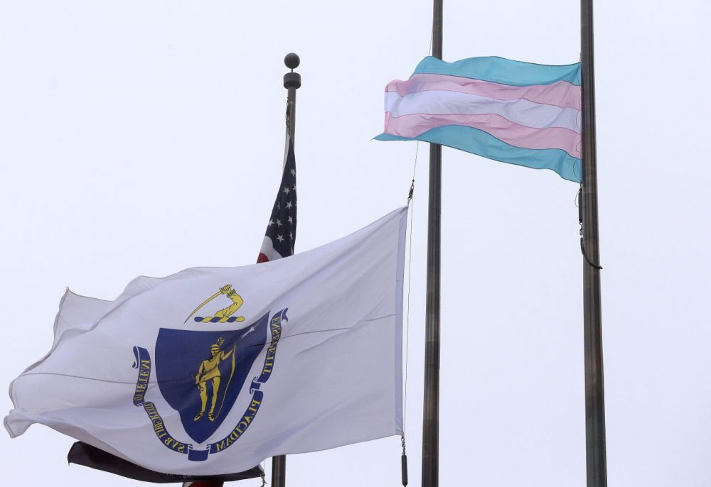 A flag representing the transgender community flies next to the Massachusetts state flag at Boston City Hall. (Steven Senne/AP)
