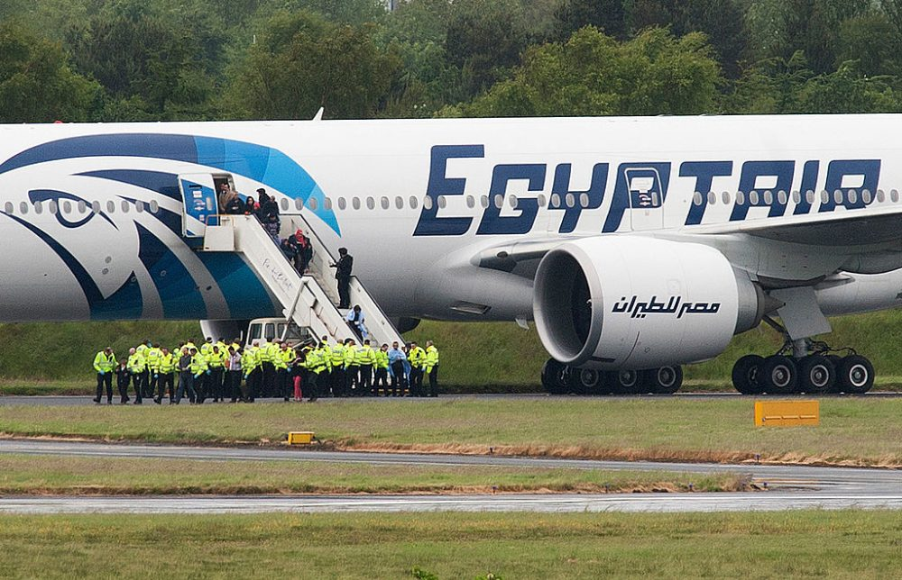 """Police escort passengers off the Egyptair Boeing 777 flight from Cairo that was forced to land at Glasgow Prestwick airport in Scotland on June 15, 2013 en route to JFK airport in New York after an onboard incident. Britain's Royal Air Force (RAF) on June 15 escorted an Egyptair plane bound for New York to a Scottish airport following an onboard incident, the Ministry of Defence said. The Boeing 777 was travelling between Cairo and New York when a passenger alerted plane crew that she had found a note reading """"I'll set this plane on fire"""" in the toilet. The message was scrawled in pencil on a napkin and was found by BBC New York producer Nada Tawfik. (Andy Buchanan/AFP/Getty Images)"""