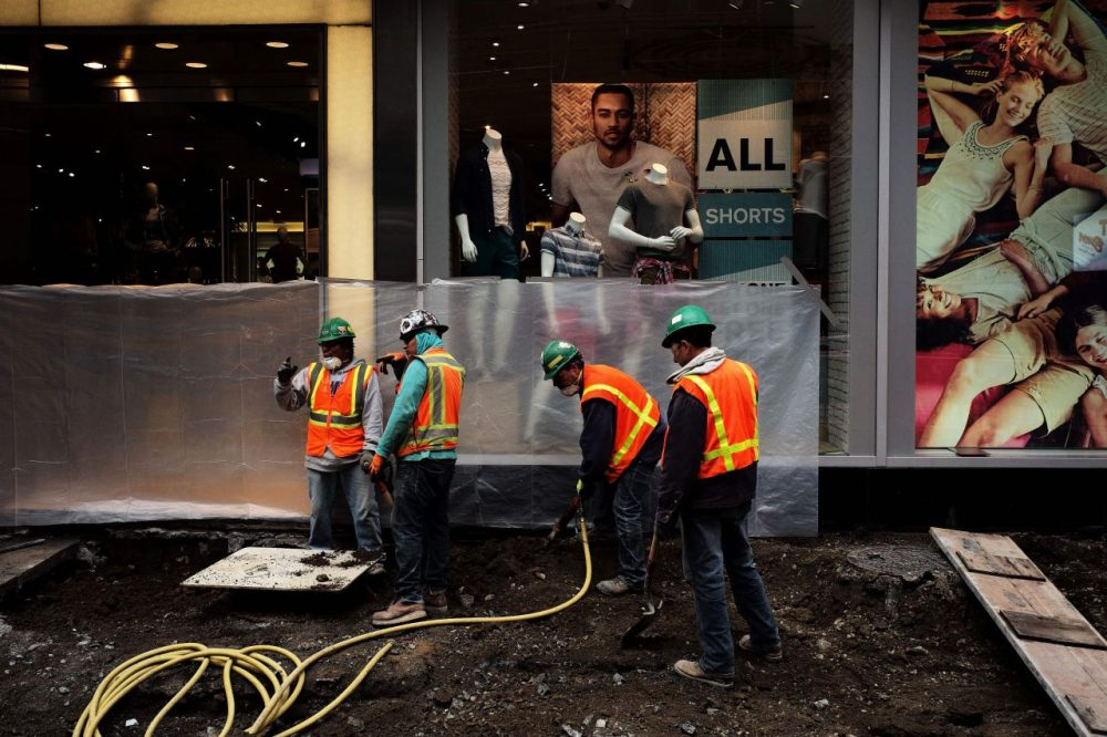 Workers dig to clear cement and soil to rebuild a footpath at the Times Square in New York on May 5, 2016. An increase in layoffs pushed US claims for unemployment insurance higher last week but the jobs market remains tight, Labor Department data showed. (Jewel Samad/AFP/Getty Images)