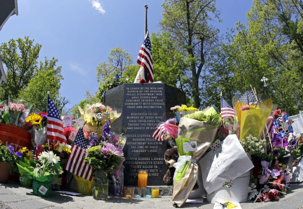 Flowers, flags, and other articles are placed as a memorial for slain Auburn Police Officer Ronald Tarentino outside the police station in Auburn. (Elise Amendola/AP)