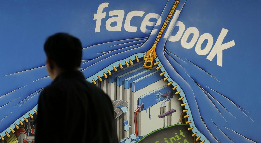 In this June 11, 2014 photo, a man walks past a mural in an office on the Facebook campus in Menlo Park, Calif. On Thursday, May 12, 2016, Facebook pulled back the curtain on how its Trending Topics feature works, a reaction to a report that suggested Facebook downplays conservative news subjects. (Jeff Chiu/AP)
