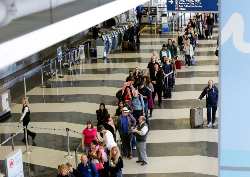 A long line of travelers wait for the TSA security check point at O'Hare International airport, in Chicago on May 16, 2016.  As airport security lines get longer, the finger-pointing over blame is growing too. (Teresa Crawford/AP)