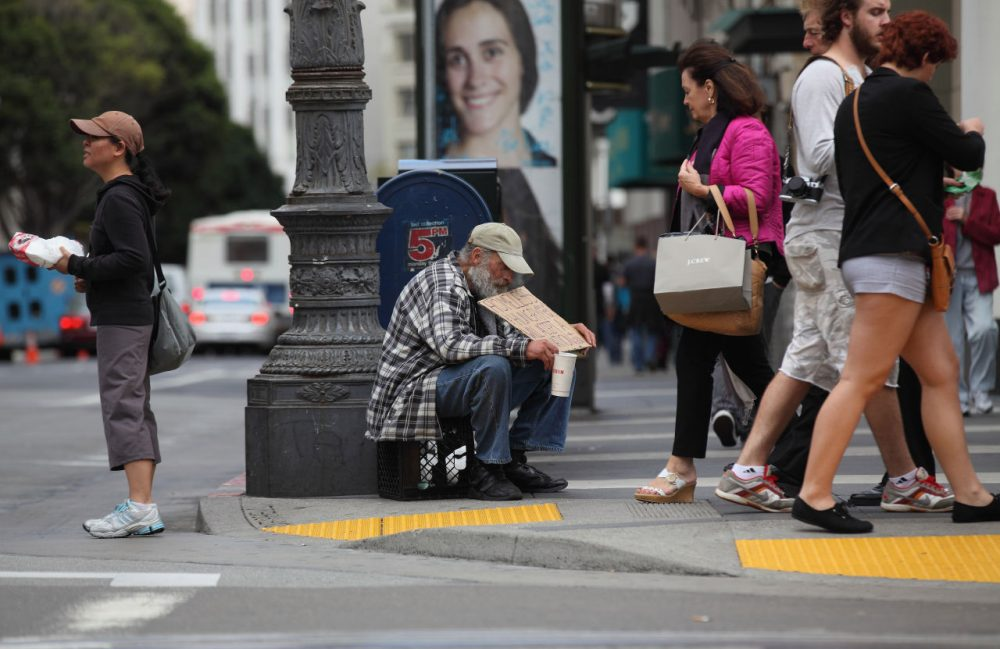 A homeless man holds a sign as he panhandles for spare change on September 16, 2010 in San Francisco, California.