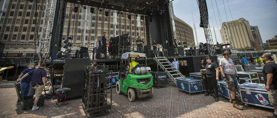 Workers begin to transform the brick City Hall Plaza Thursday for the three-day music fest over the weekend. (Jesse Costa/WBUR)