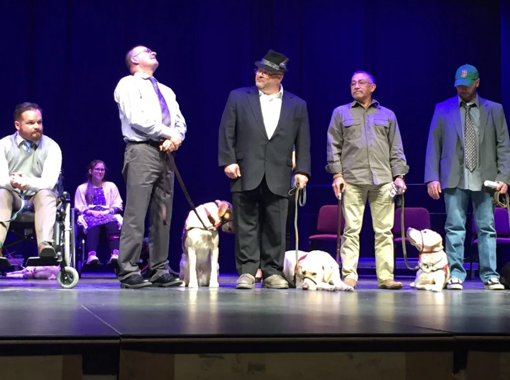 Veterans stand with their NEADS service dogs at the organization's graduation ceremony. (Robin Young/Here & Now)