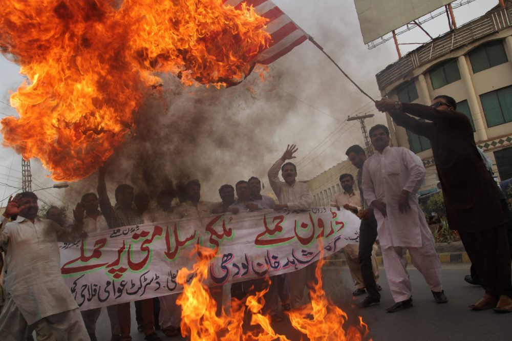 A Pakistani demonstrator holds a burning US flag as others shout slogans during a protest  in Multan on May 24, 2016, against a US drone strike in Pakistan's southwestern province Balochistan. (SS Mirza/AFP/Getty Images)