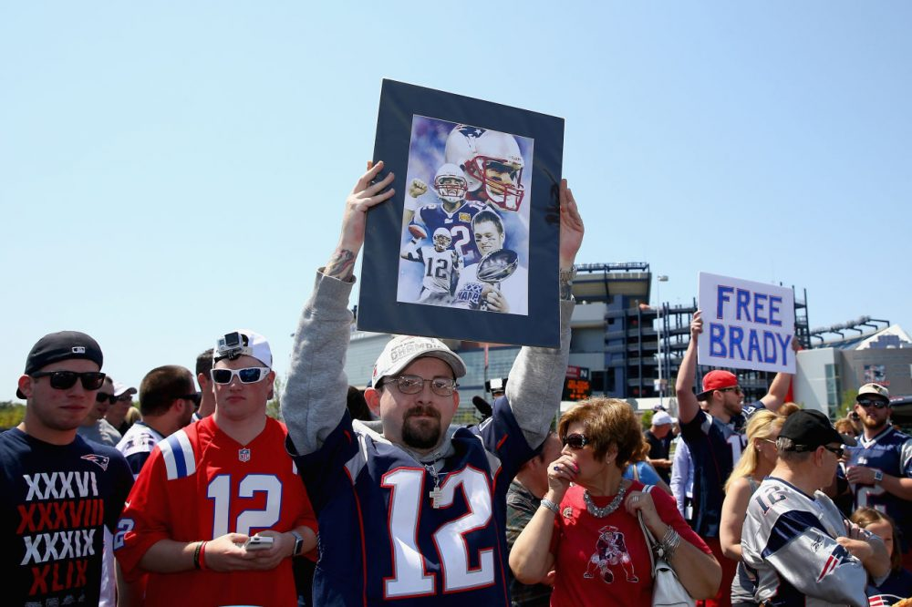 """FOXBORO, MA - MAY 24:  Paul Goodrow of Watertown, Massachusetts holds a sign in support of New England Patriots quarterback Tom Brady at the """"Free Tom Brady"""" rally at Gillette Stadium on May 24, 2015 in Foxboro, Massachusetts. The rally was held in protest of Brady's four game suspension for his role in the """"deflategate"""" scandal.  (Photo by Maddie Meyer/Getty Images)"""