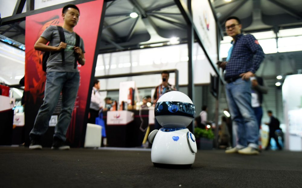 This photo taken on May 11, 2016 shows visitors watching a robot display during the first day of the Consumer Electronics Show (CES) in Asia in Shanghai. (STR/AFP/Getty Images)