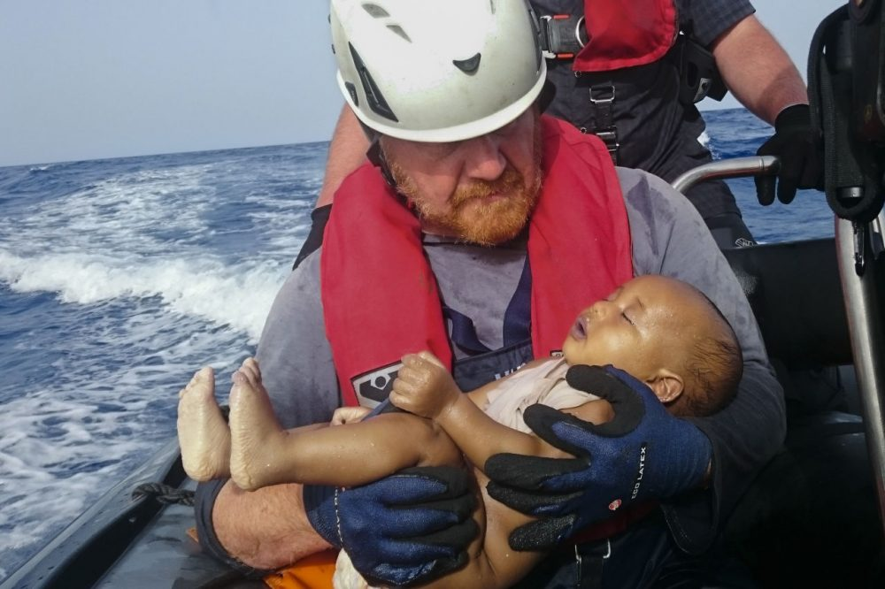 In this Friday, May 27, 2016 photo, a Sea-Watch humanitarian organization crew member holds a drowned migrant baby, during a rescue operation off the coasts of Libya. (Christian Buttner/EIKON NORD GMBH GERMANY via AP)