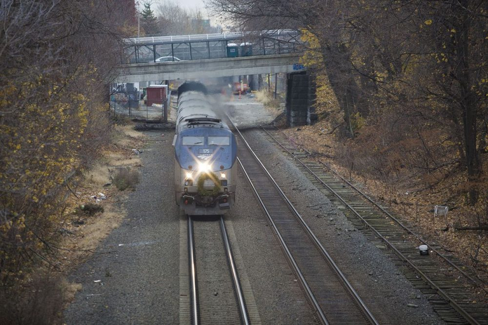 The Amtrak Downeaster barrels down the tracks. The tracks of the corridor for the proposed Green Line Extension which run through Somerville and Medford already serves MBTA Commuter Rail and Amtrak trains. (Jesse Costa/WBUR)
