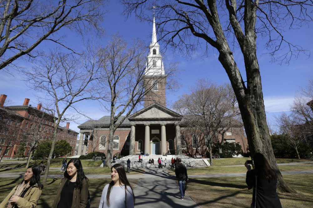In this March 13, 2016 photo, people walk near Memorial Church on the campus of Harvard University in Cambridge, Mass. The university's first female president, Drew Faust, announced Friday, May 6, 2016, that students who join Harvard's male-only social clubs won't be able to serve as sports captains or leaders of other campus groups starting in fall 2017. (Steven Senne/AP)