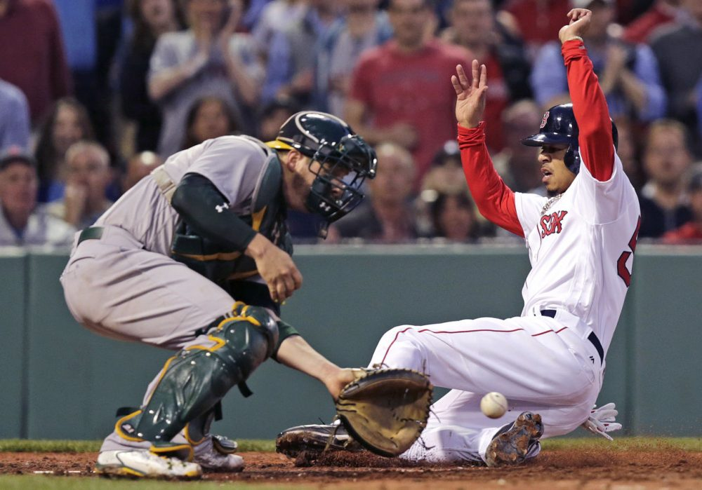 Mookie Betts slides into home for one of the Sox' 13 runs in last night's victory over the A's. (Charles Krupa/AP)
