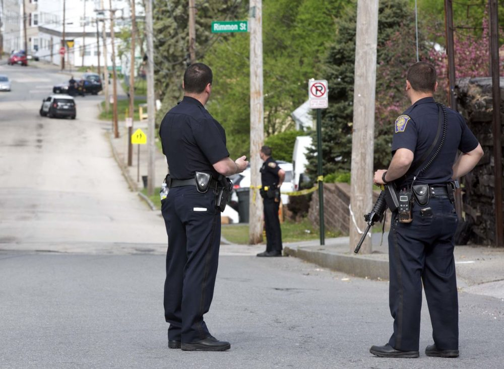 Police stand guard during the search for a suspect who shot two police officers early Friday in Manchester, N.H. (Jim Cole/AP)