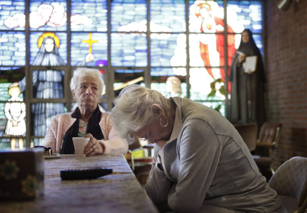 Mary Fernandes, left, and Nancy Shilts, parishioners at St. Frances X. Cabrini in Scituate, react in the church Monday while talking about its closing. The Supreme Court has refused to hear an appeal from parishioners who are occupying the church, which the Archdiocese of Boston closed more than a decade ago. (Steven Senne/AP)