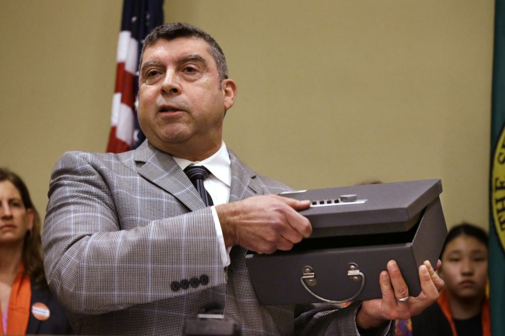 A Seattle public health official demonstrates the use of a gun lock box during a news conference on Jan. 21. (Elaine Thompson/AP)