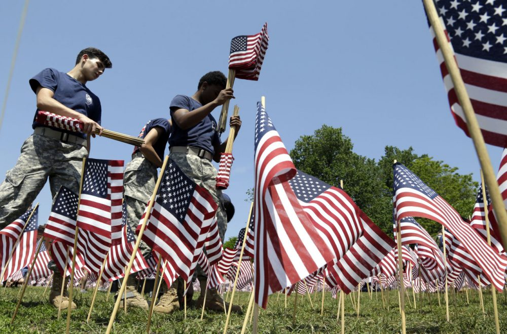 Junior ROTC members from Revere High School help to plant flags on the Boston Common. Some 37,000 flags honoring the fallen members of the military from Massachusetts since the Revolutionary War will be placed for Memorial Day weekend. (Elise Amendola/AP)