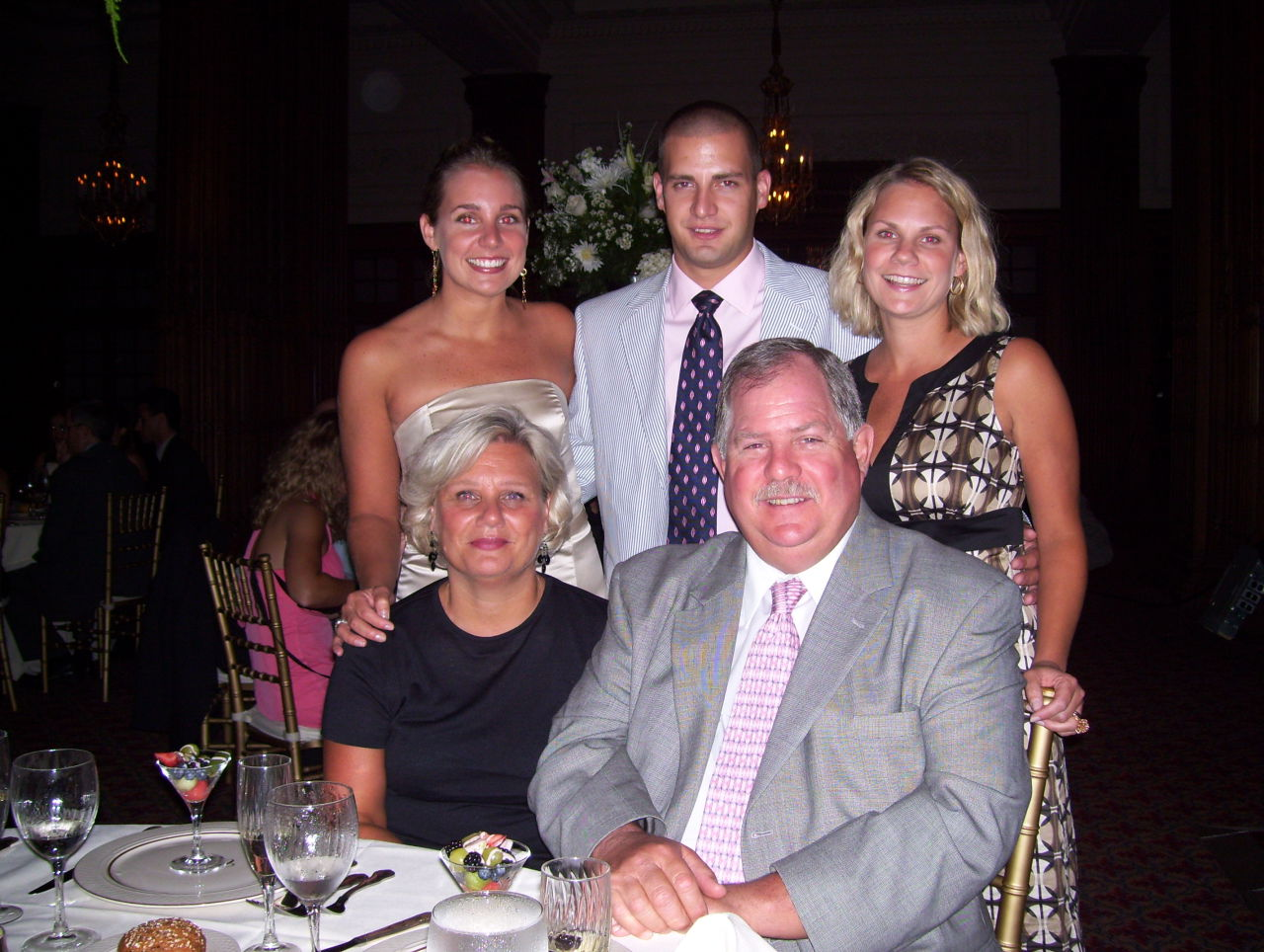 Charles Grugan, center, stands with his two sisters, Carolyn Grugan Noll, left, and Jennifer Grugan Whitehouse, right. Charles' mother, Eileen Grugan and his father, Charles Grugan Sr. sit in the front. (Courtesty/Carolyn Grugan)