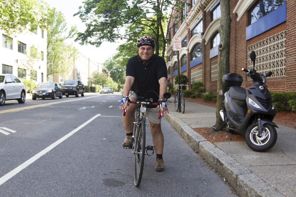 Bruce Gellerman on his bike outside WBUR's offices after both knee surgeries. (Joe Difazio for WBUR)