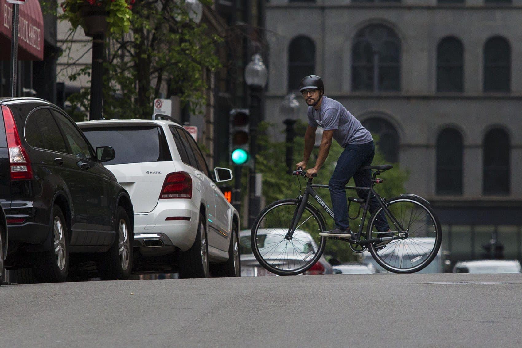 Fortified Bicycle president Tivan Amour rides on Boston's Avenue de Lafayette. (Jesse Costa/WBUR)