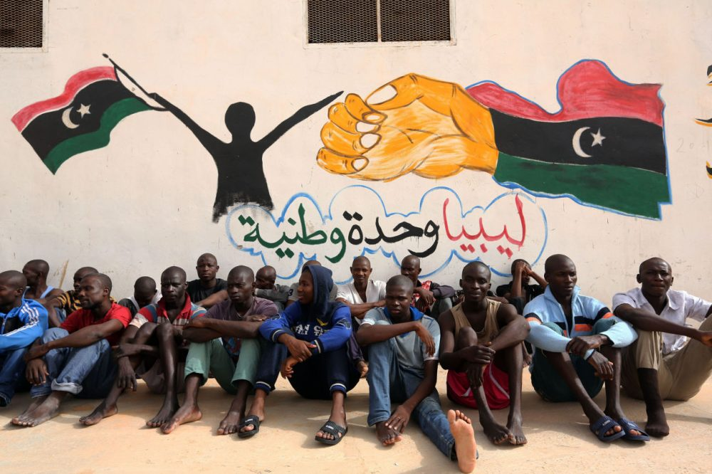 Illegal migrants sit in front of a painted wall on May 19, 2016 at the Abu Salim detention centre in the Libyan capital Tripoli during a visit of United Nations' special envoy to Libya. (Mahmud Turkia/AFP/Getty Images)