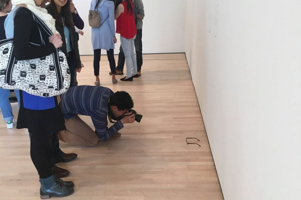 A man kneels down to take a photograph of a pair of glasses left behind by 16-year-old Kevin Nguyen at the San Francisco Museum of Modern Art in San Francisco, California. (Courtesy/Kevin Nguyen)