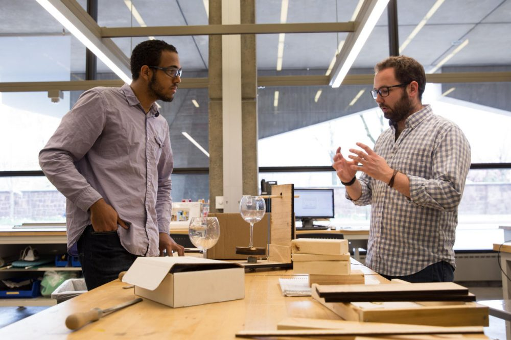 Yale student Bobby Berry talks to Yale instructor Thibault Bertrand as he works on his musical instrument project, a rotating glass harp. (Ryan Caron King/WNPR)