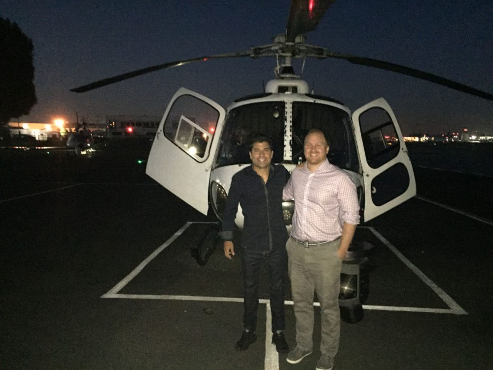 Here & Now co-host Jeremy Hobson stands with Rick Dickert, a certified broadcast meteorologist and traffic reporter for Fox 11 Morning News in Los Angeles, in front of a traffic helicopter. (Ethan Lindsey/Here & Now)