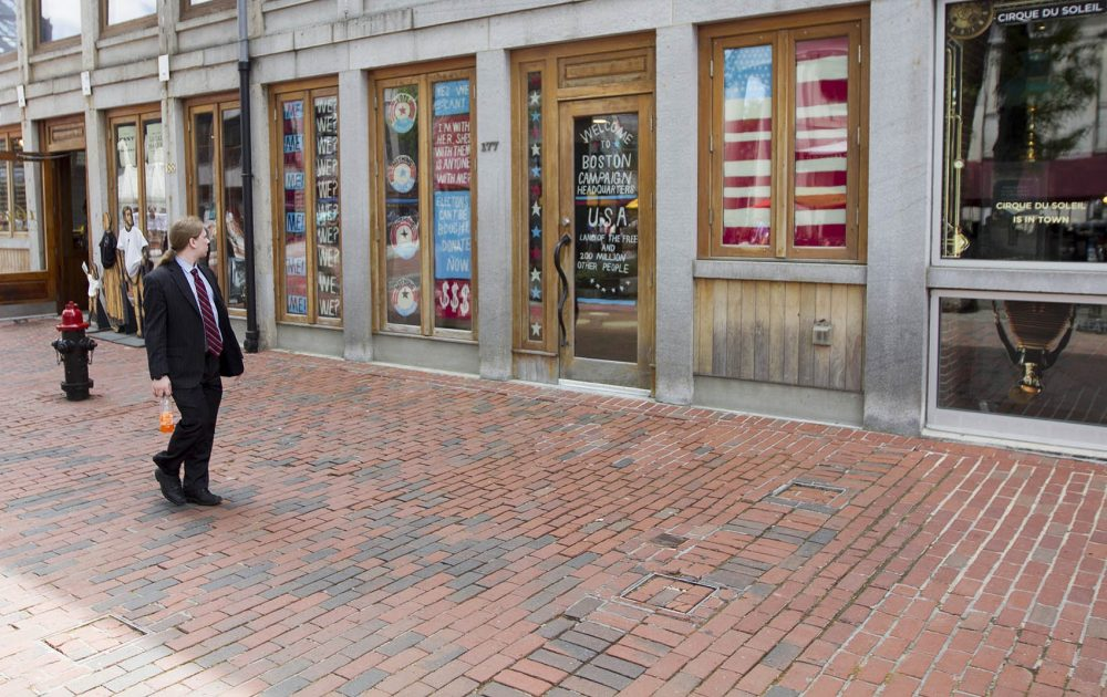 A passerby notices artist Pat Falco's faux Boston Campaign Headquarters meant to poke fun at election season. (Joe Difazio for WBUR)