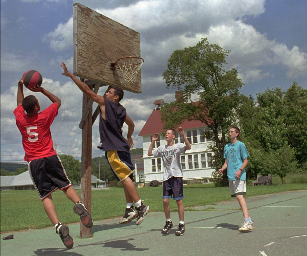 Gonzalo Ortiz, left, 16, shoots a basketball as his brother Joe Ortiz, 17, both of Brooklyn, N.Y., defends while playing in Worcester, Vt., with their Fresh Air Fund host Matt Meninger, 15, far right, and friend Patrick Harriman, 15, of East Montpelier, Vt., Friday, July 12, 1996.  Gonzalo Ortiz has been coming to Vermont through the program each summer since he was four-years-old. (Craig Line/AP)