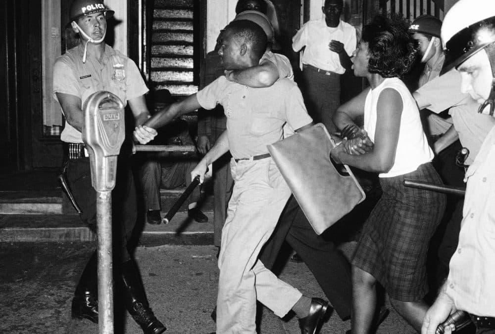 Steel-helmeted police pull a demonstrator toward police van as they arrest him during rioting in Philadelphia's North Side, August 1964. (AP)