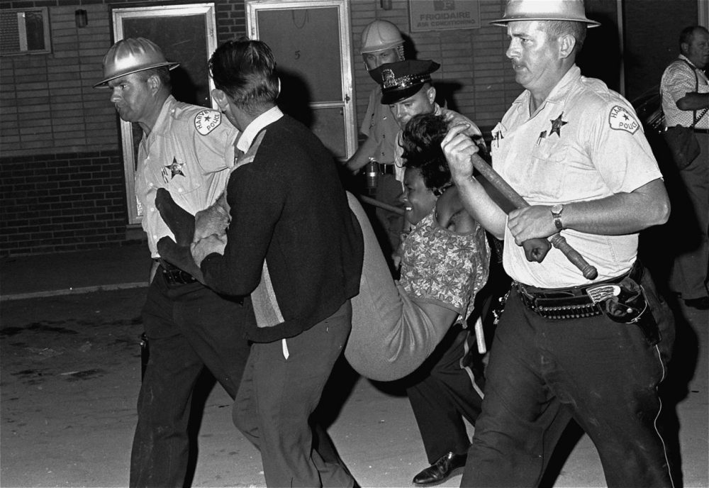 A woman who stayed at the riot scene in Dixmoor, Illinois in August 1964 is carried to a police van. More than a score were arrested. (AP)