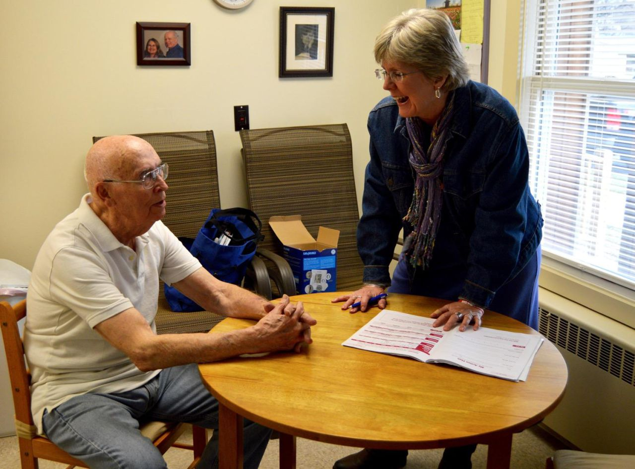 Karyn Crossman, a SASH coordinator pays a visit to 88-year-old Lloyd Piggrem, of Rutland. Piggrem is one of 100 clients Crossman works with through a statewide nonprofit that provides a variety of home-based support services. (Nina Keck/VPR)