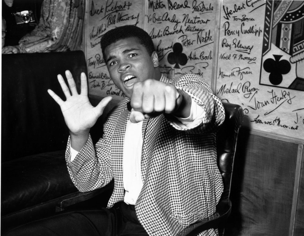 American boxer Cassius Clay, who later changed his name to Muhammad Ali, holds up five fingers in a prediction of how many rounds it will take him to knock out British boxer Henry Cooper.  (Kent Gavin/Keystone/Getty Images)