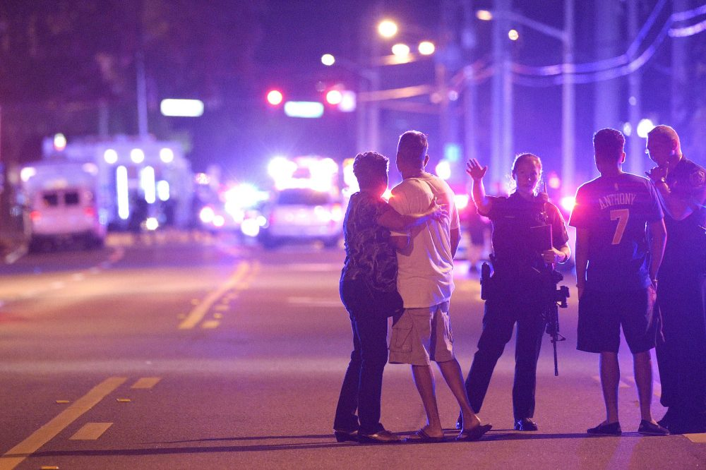 Orlando Police officers direct family members away from a fatal shooting at Pulse Orlando nightclub early Sunday. (Phelan M. Ebenhack/AP)