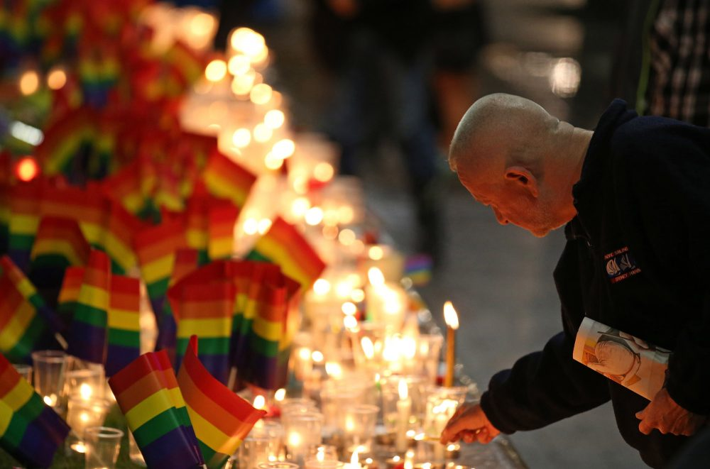 "A man places a candle at an impromptu memorial set up in Sydney on Monday following the Orlando attack. Australian Prime Minister Malcolm Turnbull said that the Orlando mass shooting was ""an attack on all of us, —on all our freedoms, the freedom to gather together, to celebrate, to share time with friends."" (Rick Rycroft/AP)"
