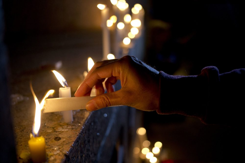 A man lights a candle during a vigil in front of the U.S. embassy in Santiago, Chile to remember the victims. (Esteban Felix/AP)