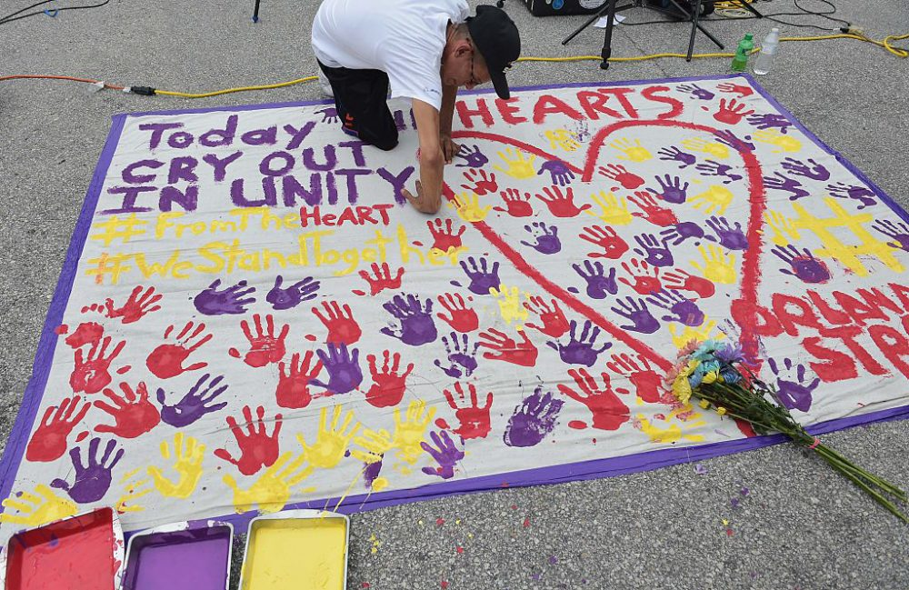 A man places a hand print on a makeshift memorial in a parking lot near the Pulse nightclub in Orlando, Florida on June 12, 2016. (Mandel Ngan /AFP/Getty Images)