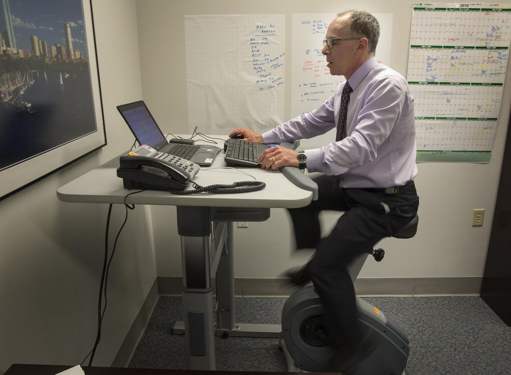 Eddie rides an exercise bike as he works in his office at the VA Boston Healthcare System. (Robin Lubbock/WBUR)