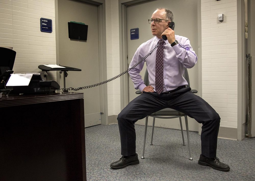 Dr. Eddie Phillips squats as he talks on the phone at his office. (Robin Lubbock/WBUR)