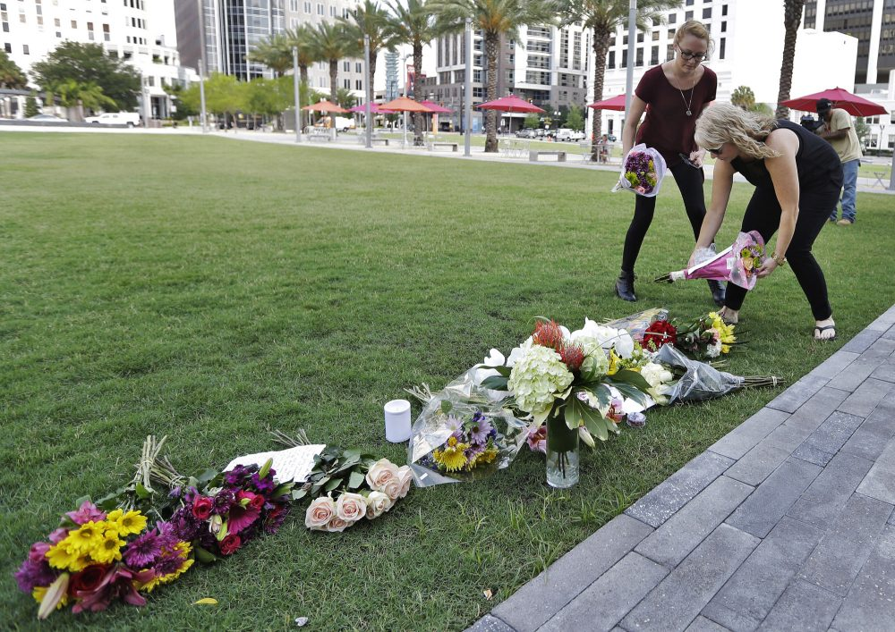 Two women place flowers for the victims of the fatal shootings at Pulse Orlando nightclub at a makeshift memorial in Orlando, Fla. on Monday. (Chris O'Meara/AP)