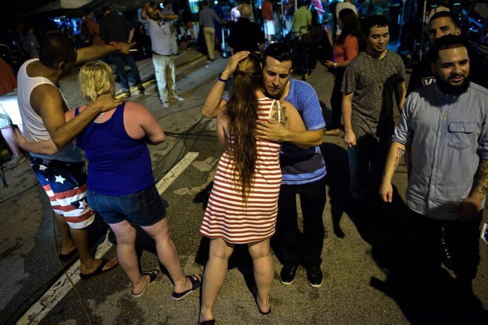 People hug after praying near the Pulse nightclub on June 12, 2016 in Orlando, Florida. (BRENDAN SMIALOWSKI/AFP/Getty Images)